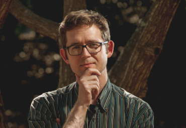 Gregory Frye, writer, standing in front of trees with glasses on and an inquisitive expression